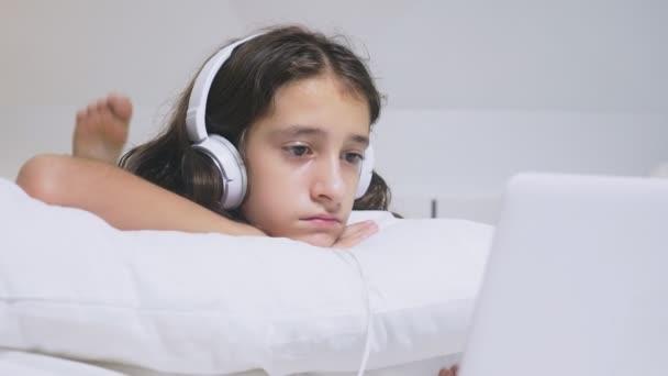 Dívka teenager v sluchátka v šoku, co se děje na obrazovce svého notebooku, protože byla sama. Koncepce bezpečnosti internetu pro děti