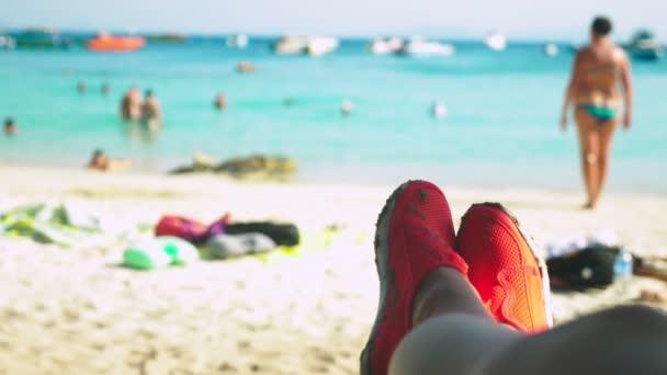 közeli kép a női lábak, piros cipő, az úszás, a háttérben az azúrkék beach, életlenítés háttér