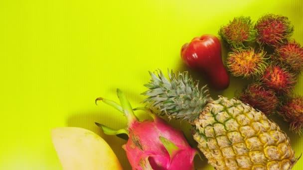 ruce si tropické ovoce s jasně žlutým pozadím. Minimální ovoce concept.