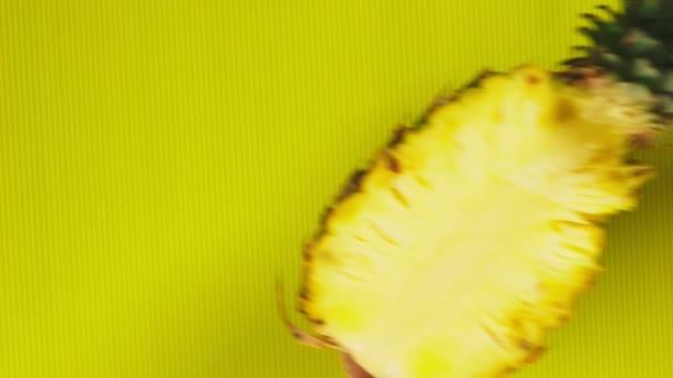 Frauenhände legen Ananas auf einen leuchtend gelben Hintergrund. Minimales Fruchtkonzept.