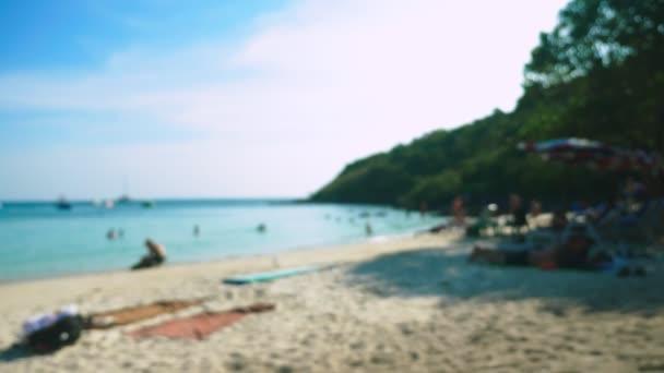 abstraktní rozostření pozadí pláže na ostrově, odpočívající lidé a lodě.