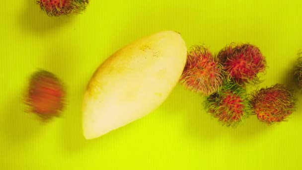 tropical fruit on a bright yellow background. rambutans and yellow mangoes. Minimal fruit concept.