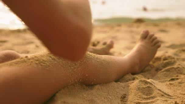 hosszú lábú lány a strandon, öntés homok a lábát