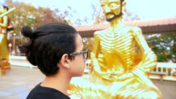 A buddhizmus. worshiping arany Buddha szobrok fiú