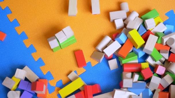 Koncepce vzdělávání. Vícebarevné dřevěné cihly, bloky hračka, z ptačí perspektivy na pozadí obrovské puzzle. kopie prostor