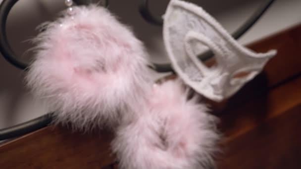 PelzHandschellen und Spitzenmaske auf dem geschmiedeten Kopfteil. Nahaufnahme