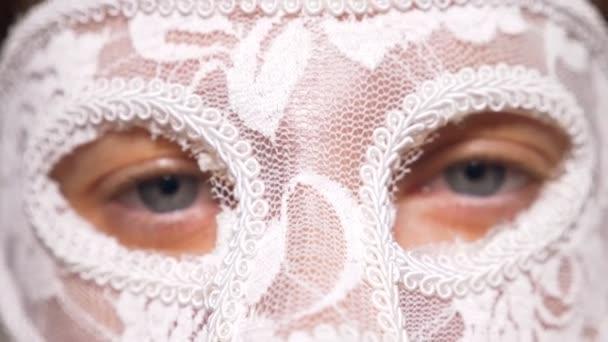 weiße Spitze Maske auf ein Womans Gesicht Nahaufnahme. blaue Augen blicken in die Kamera durch die Maske im Gesicht