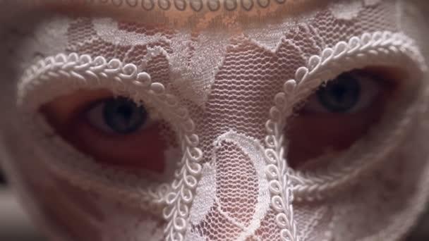 weiße Spitzenmaske auf einem Frauengesicht, Nahaufnahme. Blaue Augen blicken durch die Maske auf seinem Gesicht in die Kamera.