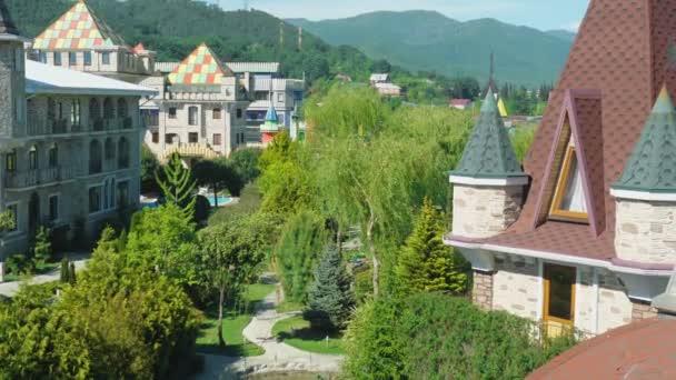 Luxushotel im viktorianischen Stil, umgeben von wunderschönen Bäumen und Sträuchern. Dächer mit Kirchtürmen auf dem Hintergrund eines Bergrückens und einem klaren blauen Himmel. aus der Höhe