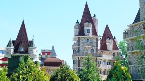 Luxushotel im viktorianischen Stil, umgeben von wunderschönen Bäumen und Büschen. Dächer mit Kirchtürmen vor blauem Himmel