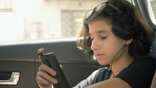 happy teen boy in headphones uses phone in car