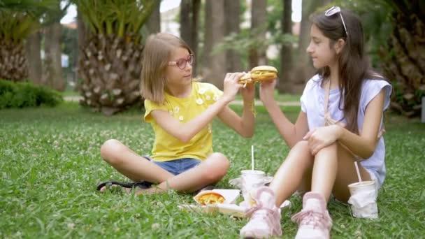 diákok piknik koncepció. két lány barátnője esznek hamburgert és sült krumplival ül a fűben a parkban