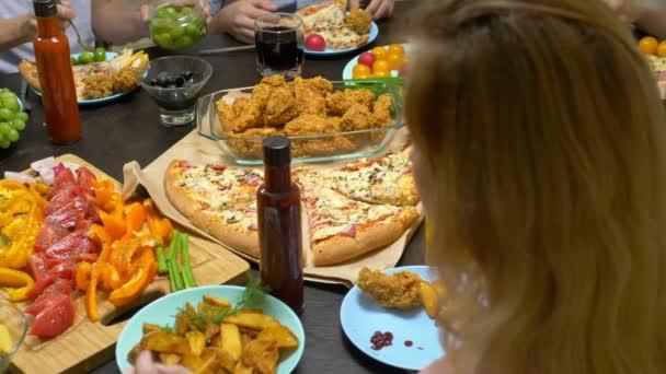 Rodina jí v útulném domácím prostředí. Domácí jídla, domácí Pizza. Šťastná rodina obědvá společně v dostatečně položeně obývacím stole