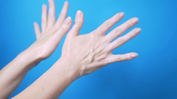 Jemné ženské ruce s přirozenou manikúru se krásně pohnou na modrém pozadí. Místo pro text.