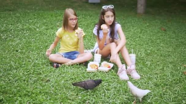 Nette Mädchen sitzen auf dem Gras im Park und füttern die Vögel mit Pommes