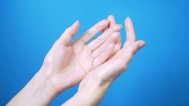 Gyengéd női kezek természetes manikűr mozog szépen a kék háttér. Szöveghely.