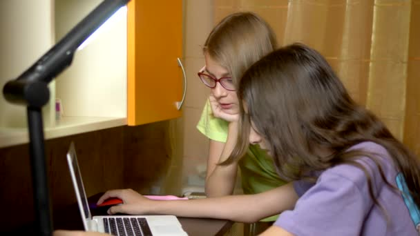 Two girls girlfriends, teenagers students sit together at the training table and use a laptop in the evening. they are cheerful and happy