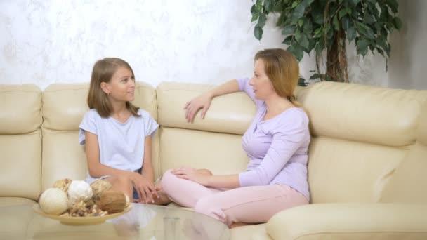 komunikační koncept matka a dcera. matka a dcera si spolu s dcerou popovídali v obývacím pokoji na pohovce