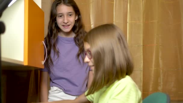 Dvě dívky Přítelkyně, Teenageři sedí pohromadě u tréninkového stolu a večer používají přenosný počítač. jsou veselé a šťastné