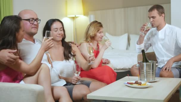 free relationship concept, swingers clubs. five young people drink champagne and exchange partners at a home party