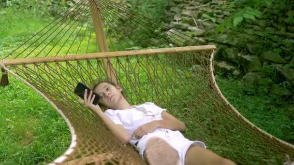 dívka používá smartphone, zatímco leží v houpací síti pod stromem na pikniku v lese