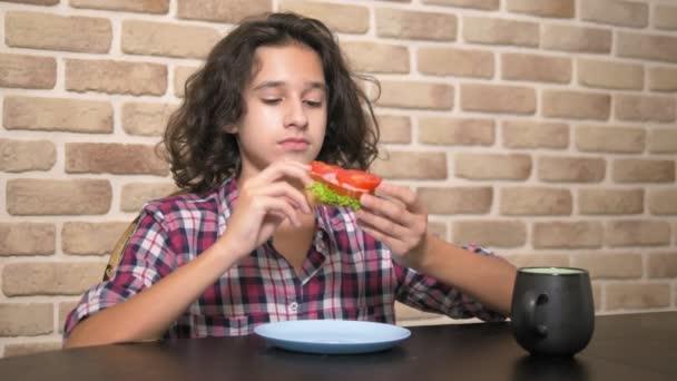 hungriger Teenager mit Appetit isst ein Sandwich mit frischem Salat und Tomaten in der Küche im Loft-Stil gegen eine Ziegelwand
