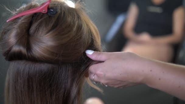 Close-up. Profesionální kadeřník používající kulmu. Kadeřnictví v salonu,