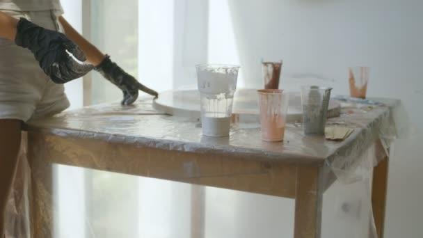 Mädchen arbeiten mit Acrylfarben in einem kreativen Studio, der Prozess der Herstellung von Acrylfarben