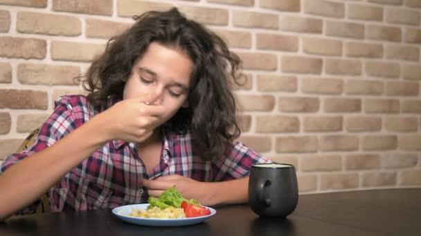 hungriger Teenager mit Appetit isst Farfalle, Pasta verneigt sich in der Küche im Loft-Stil vor einer Ziegelwand