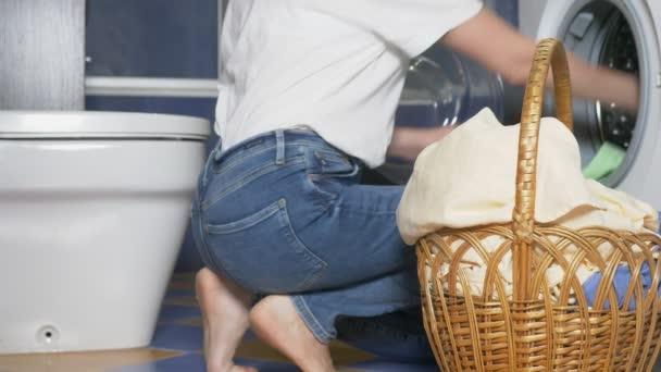 Nahaufnahme. Unerkennbare Frau legt Tuch aus Wäschekorb in Waschmaschine