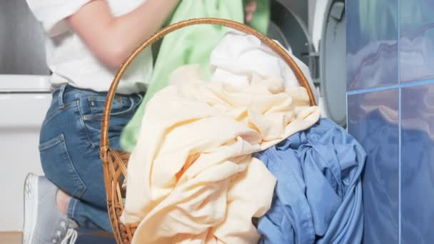 close-up. unrecognizable woman putting cloth in washing machine from laundry basket