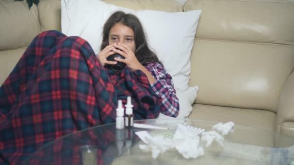 krankes Teenie-Mädchen unter der Decke trinkt ein Heißgetränk auf der Couch