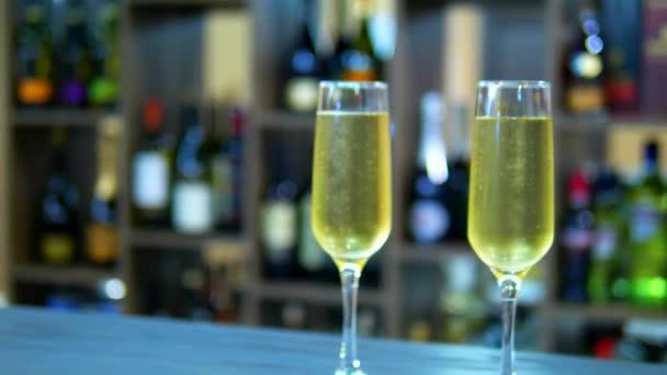 Urlaubskonzept, Datum. zwei Gläser mit Champagner auf dem Hintergrund eines Regals mit Flaschen