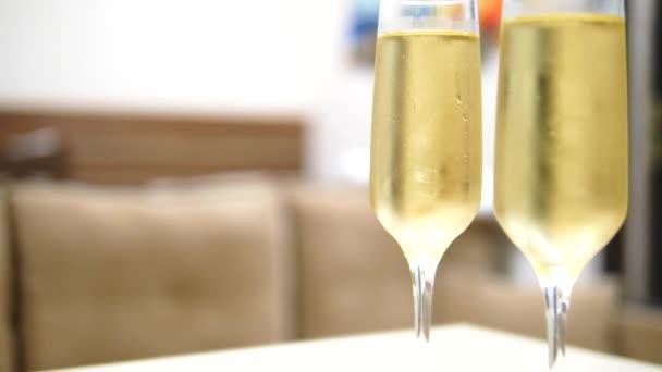 zwei Gläser Champagner auf verschwommenem Hintergrund im Inneren eines Luxushotels.