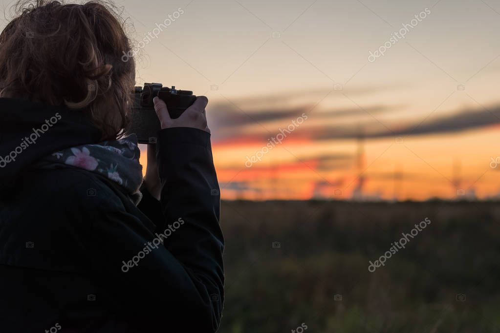 Young lady taking photos of beautiful dusk, using antiques film camera
