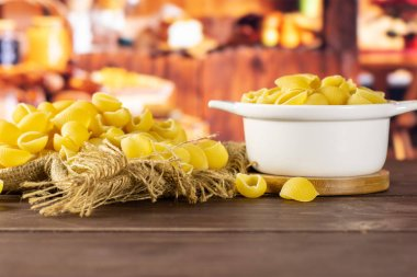 Lot of whole raw yellow pasta conchiglie variety on jute cloth in a ceramic stewpan with rustic wood kitchen in background