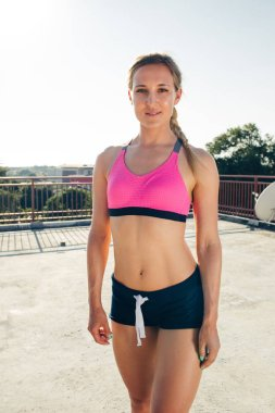 smiling young sportswoman looking at camera on rooftop