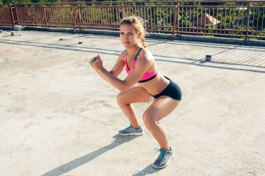 young sportswoman doing squat exercise on rooftop