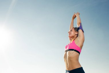 low angle view of young sportswoman in earphones with smartphone in running armband case stretching against blue sky