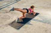 Fotografie zadní pohled na sportovkyně dělat aerobní cvičení na fitness mat