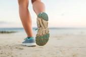 Fotografie Oříznout záběr ženské běžec běží na písečné pláži
