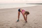 atleta femminile in auricolari fa esercitazione sulla spiaggia