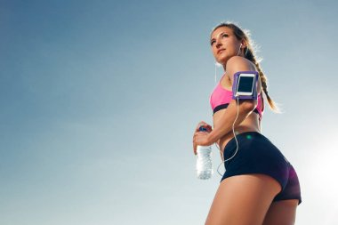 low angle view of sportswoman in earphones with smartphone in running armband case holding bottle of water on rooftop
