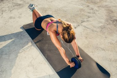 high angle view of sportswoman in earphones doing exercise with abs roller on fitness mat