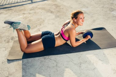 smiling sportswoman in earphones doing exercise with abs roller on fitness mat on rooftop