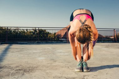 female athlete in earphones stretching on rooftop