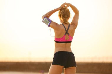 rear view of sportswoman with smartphone in running armband case standing on beach
