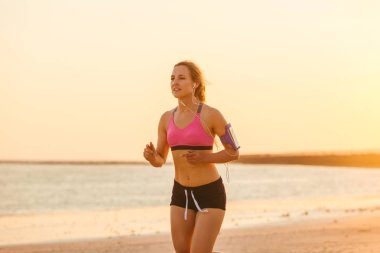 female jogger in earphones with smartphone in armband case running on beach with sea behind