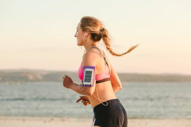 side view of smiling sportswoman in earphones with smartphone in running armband case jogging on beach with sea behind