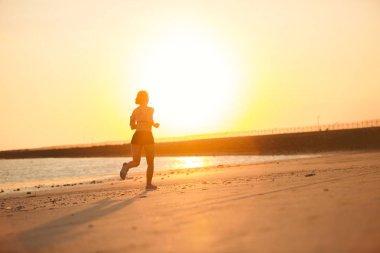 Silhouette of female jogger running on beach against sunlight stock vector